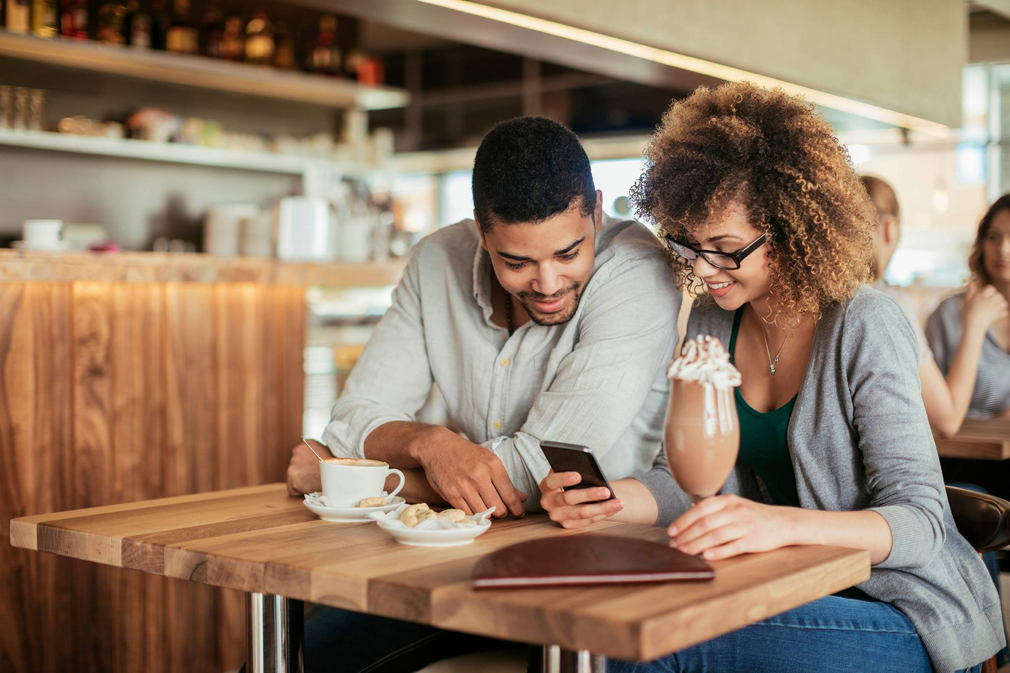 couple in cafe looking at phone to open a high interest checking account