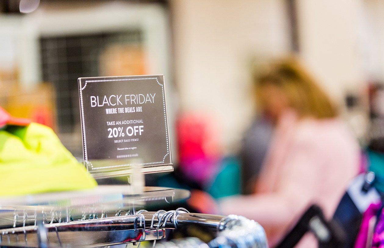 black Friday sales sign on top of clothing rack