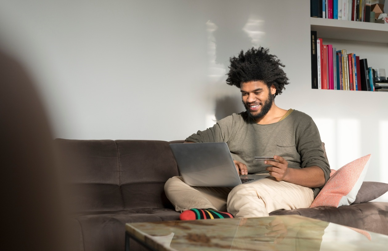 Young man sits on couch in living room. He smiles as he holds his credit card and looks at his laptop resting on his lap.