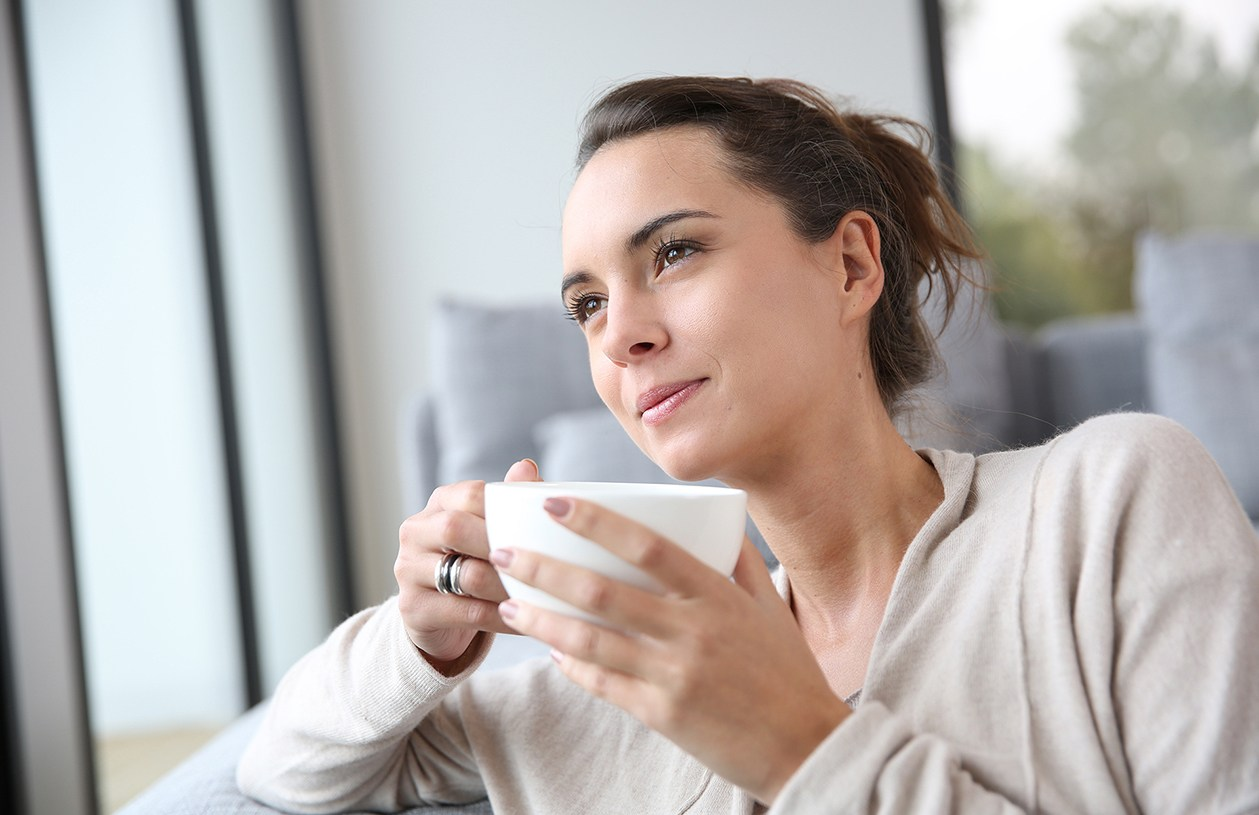 woman drinking tea while gazing out a window