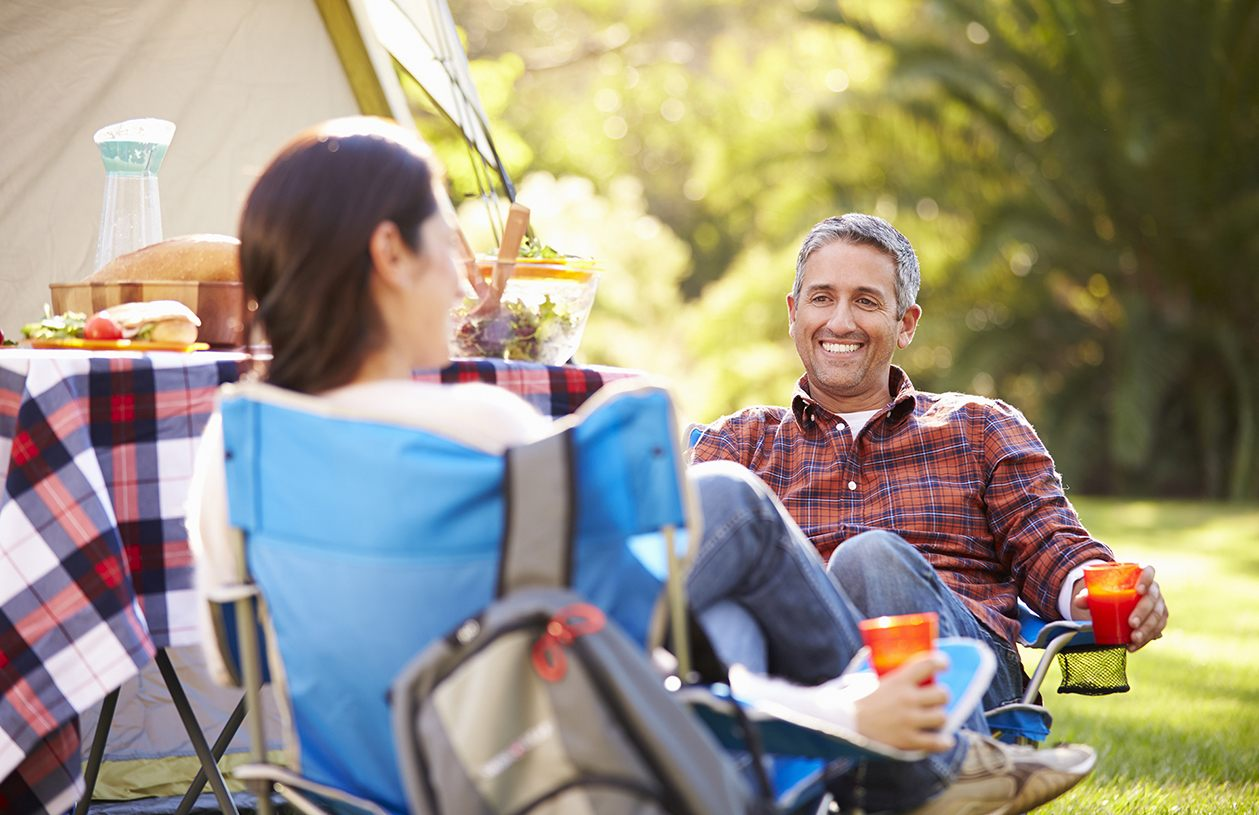 smiling couple enjoying a romantic picnic out in the woods