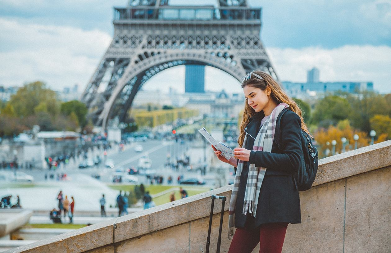 young woman stands on a bridge with the Eiffel Tower in the background looking at map next to her suitcase