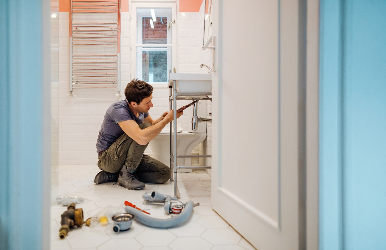 A plummer repairs a bathroom.