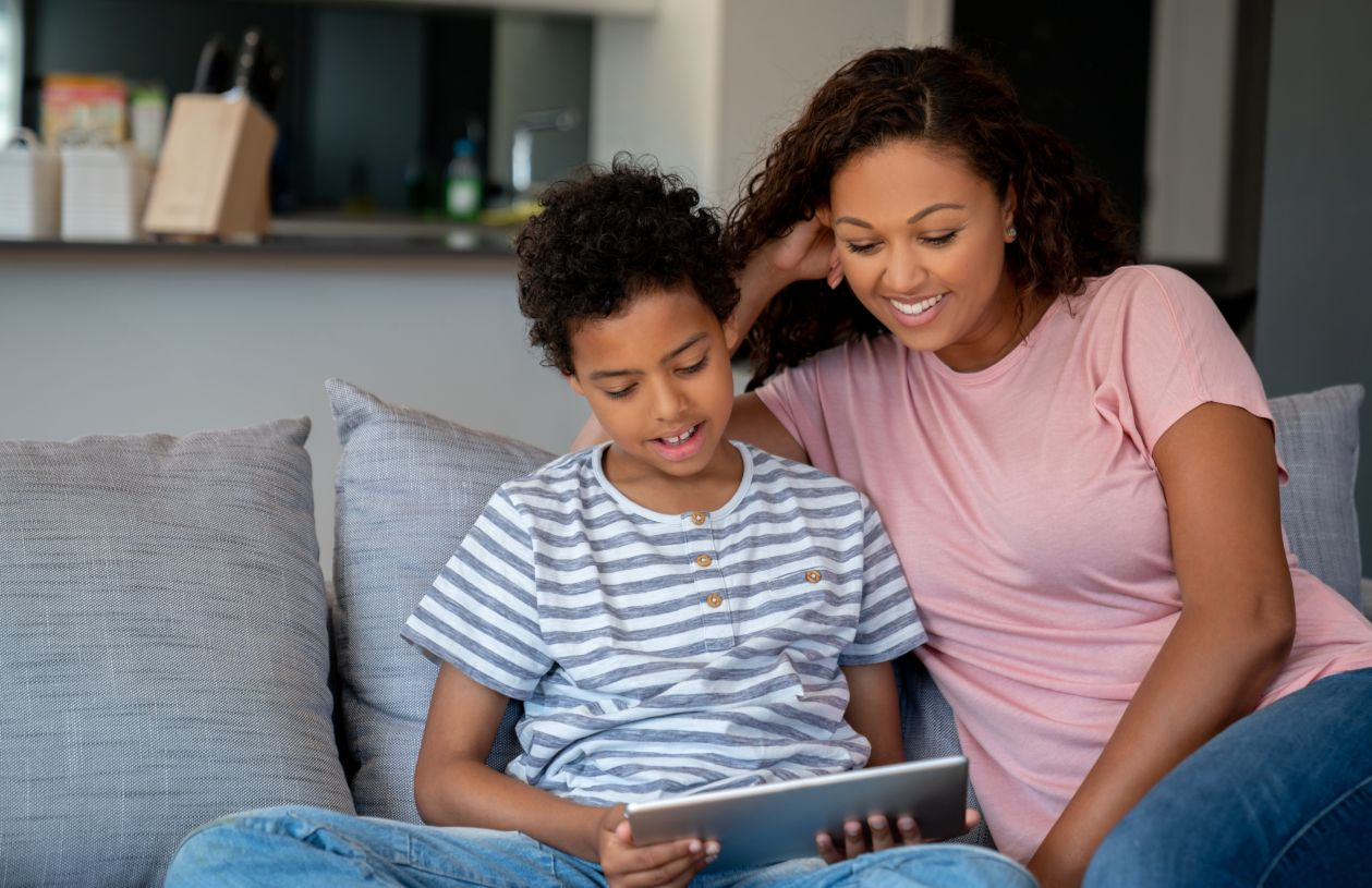 A mom helps her son research debit card options.