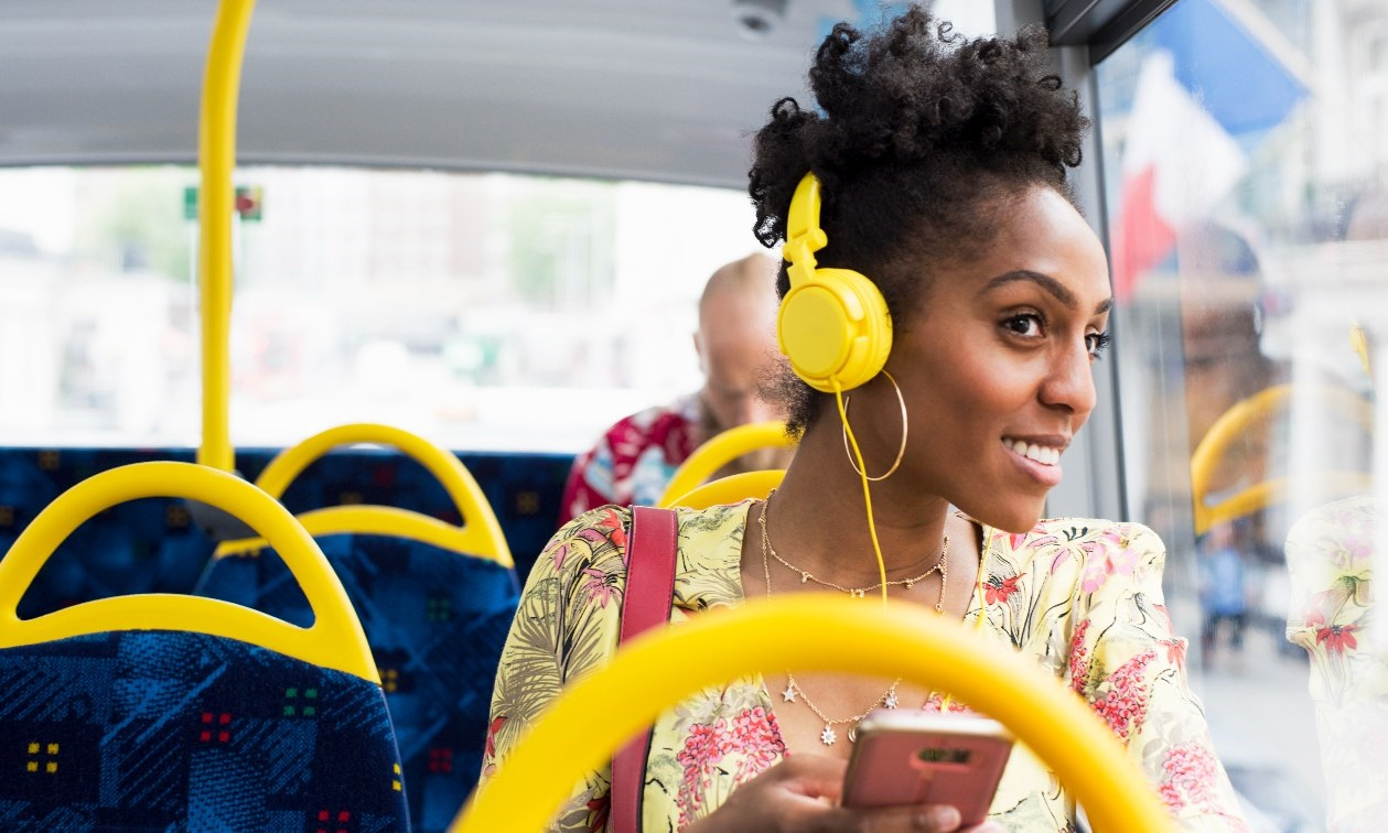 Young woman looks out the window of a bus with yellow earphones on her head. She holds her cellphone in her hand and smiles.