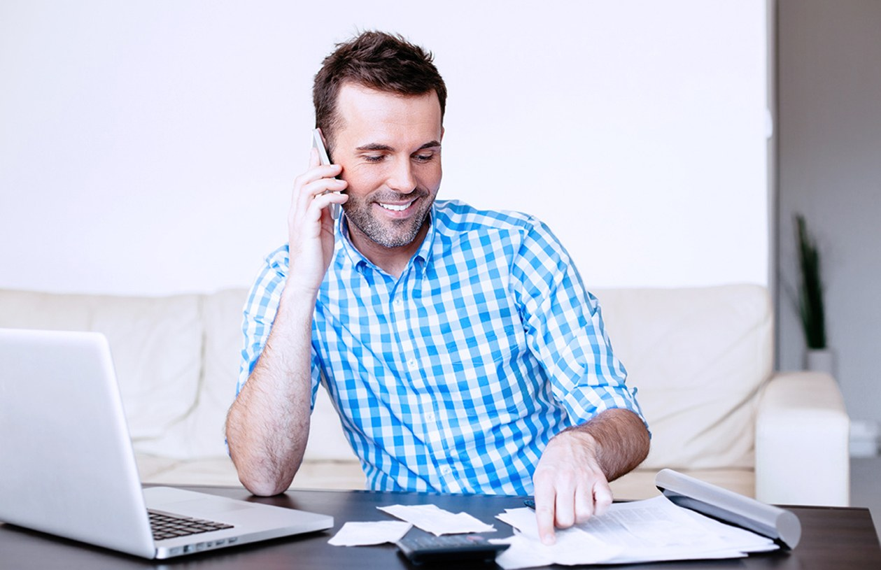 Smiling man in blue and white checkered shirt on mobile phone paying bills on his laptop