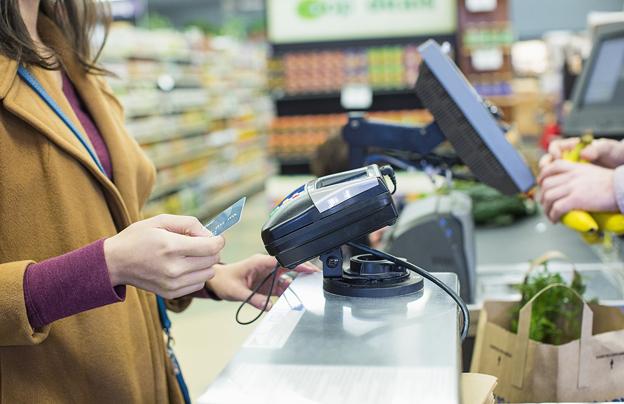 woman shopping at grocery store with store credit card
