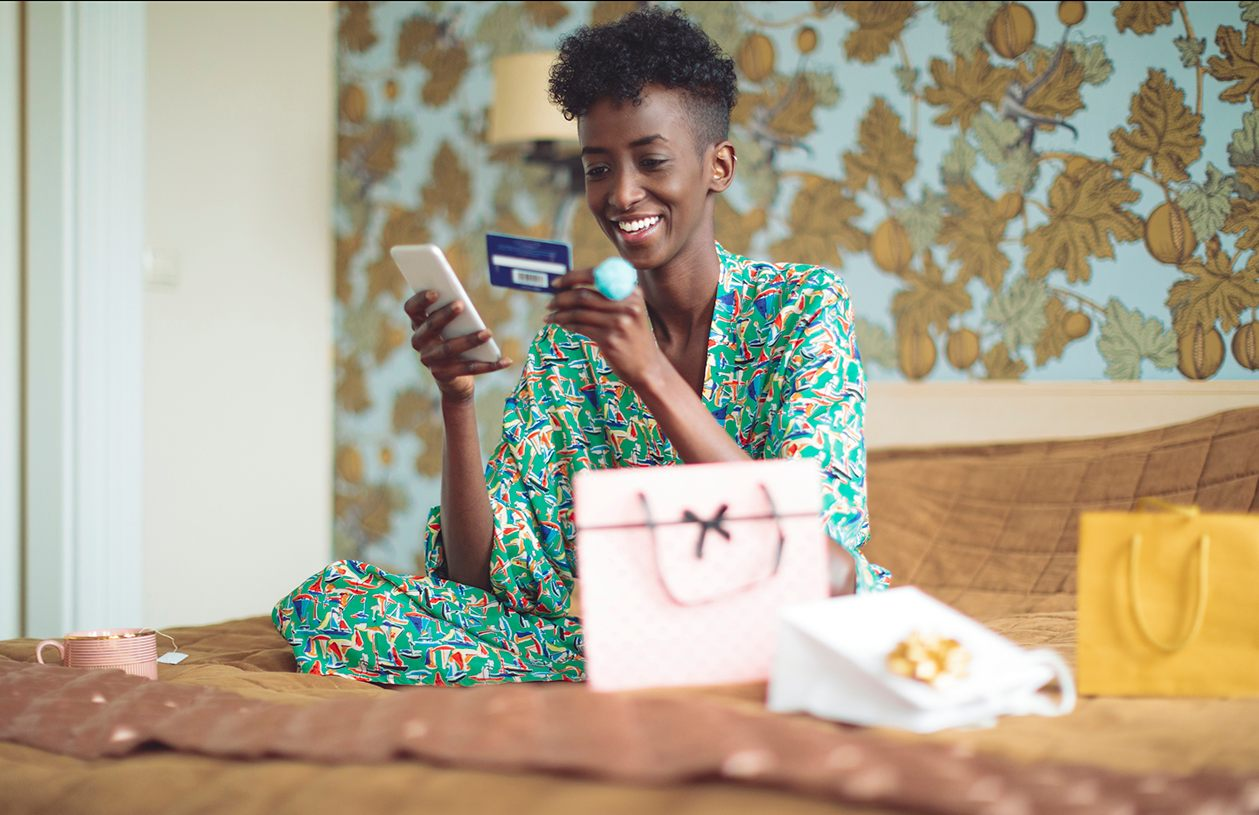 A woman smiles while looking at her credit card and mobile phone