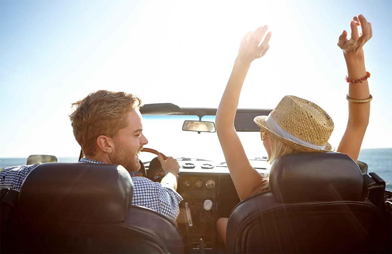 smiling couple driving in convertible  to beach