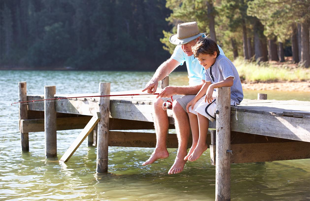 Retired grandfather and young boy sitting on a deck fishing