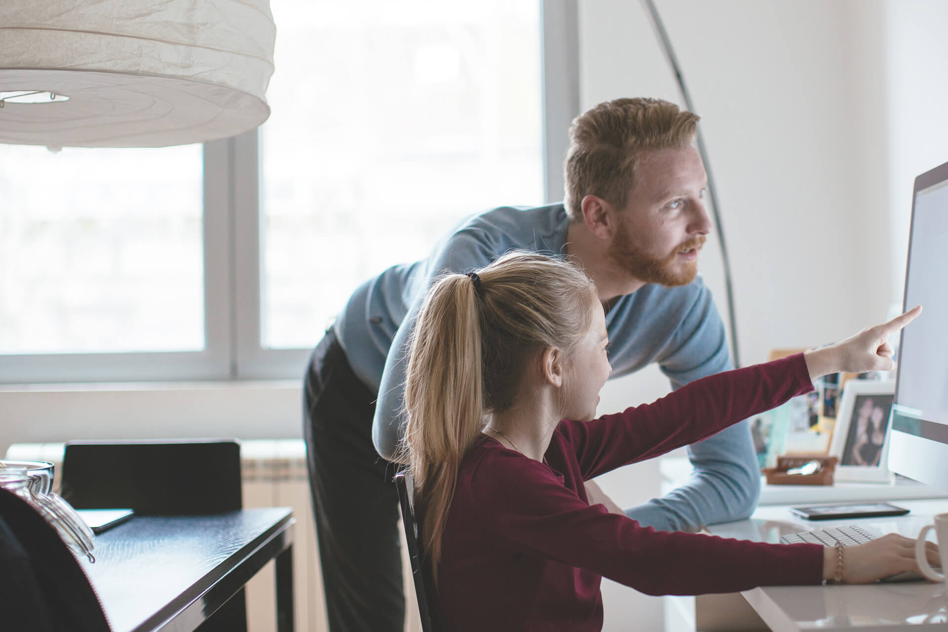 Father showing daughter her teen checking account on computer