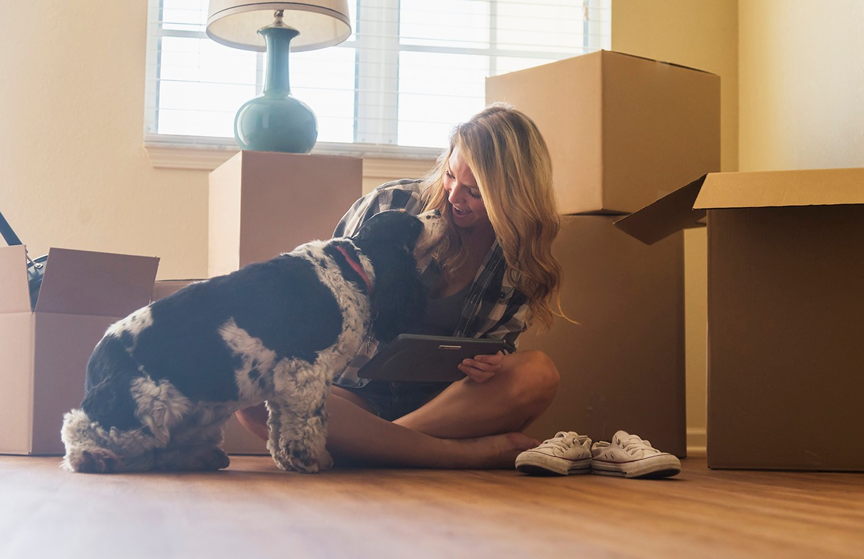 woman with dog surrounded by boxes after moving into new home
