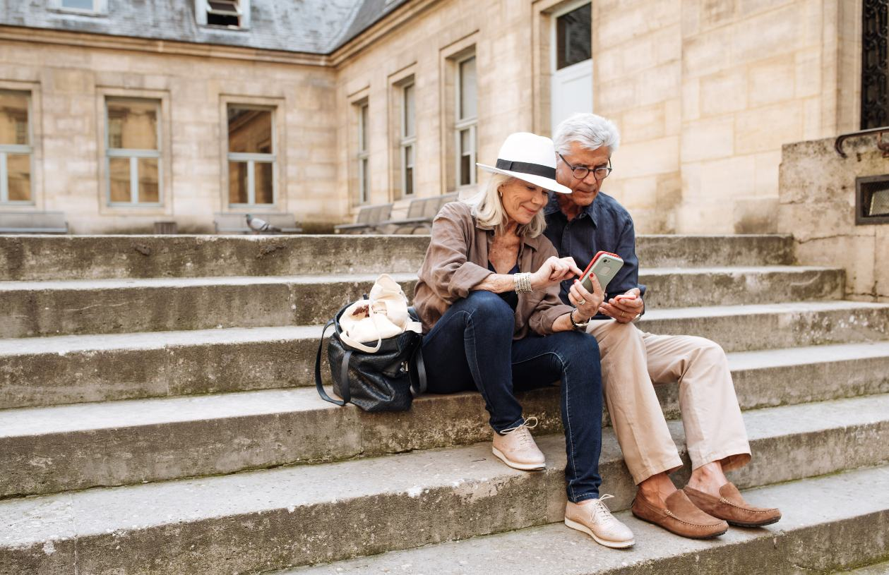 Mature husband and wife sit on steps in Paris, taking a selfie.