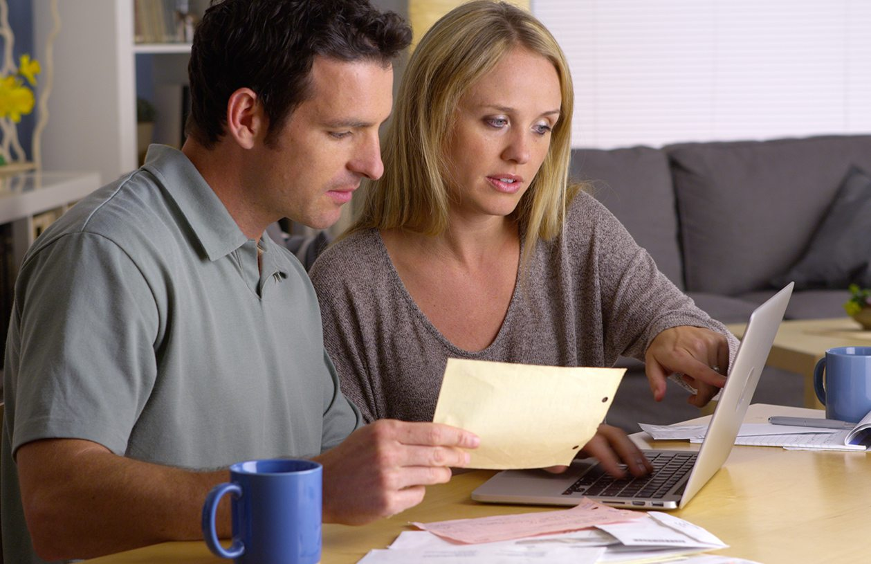 Man and woman looking at laptop considering a roth ira